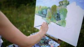 Charmigt kvinnasammanträde på plädet på parkera i solig sommardag och den avslutande attraktionbilden vid vattenfärgen målar a stock video