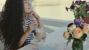 Charmigt lockigt brunettdrinkkaffe och tycker om en natursikt på sommarterrassen stock video