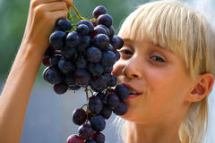 Charming. Summer vacation. Blue grapes and  charming girl Royalty Free Stock Image