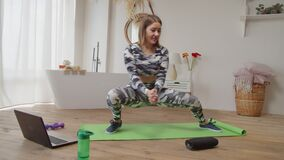Charming active sporty fit female performing low side lunge stretch during online fitness class