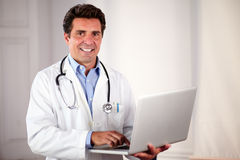 Charming adult doctor using his laptop Stock Photo