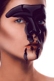 Charming adult girl with black paint on face looking at camera Royalty Free Stock Photography