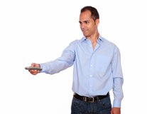 Charming adult man pointing with remote control Royalty Free Stock Image