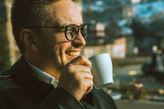Charming adult man smiling and drinking coffee Stock Photos