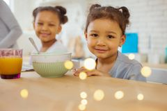Charming African girl looking straight at camera. Time to eat. Cute dark-skinned kids expressing positivity while having breakfast together royalty free stock photos