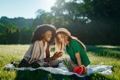 Charming african girl with pretty smile is showing something funny on a phone to her caucasian blonde girlfriend during. The picnic on the sunny meadow royalty free stock images