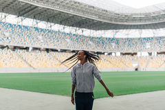 The charming afro-american sportwoman in the earphones is shaking the hair on the stadium. Royalty Free Stock Images