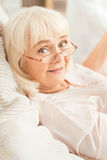 Charming aging lady lying in the bed at home. Enjoying my retirement . Smiling cheerful elderly woman sitting on the bed at home while expressing positivity and stock photography