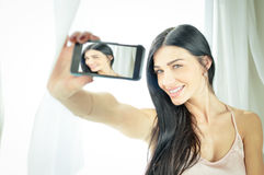 Charming amazing girl in camisole making selfie. Portrait of beautiful exciting young woman in silk camisole making selfie beside morning window. Charming girl royalty free stock photo