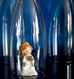 Charming angel. Toy angel between the glass on blue background Stock Photos