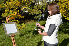 Charming artist in a park. Pretty female artist drawing autumn landscape in a city park Royalty Free Stock Image