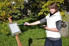 Charming artist in a park. Pretty female artist drawing autumn landscape in a city park Stock Image