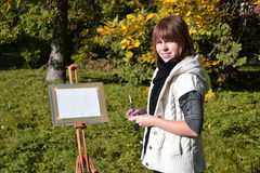 Charming artist in a park. Pretty female artist drawing autumn landscape in a city park Stock Photography