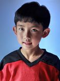 Charming Asian Boy. Asian boy wearing a sports jersey posing in studio, with special lighting to one side. Isolated on blue background Stock Image