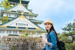 Female holding guidebook and looking happy. Charming asian female holding guidebook with both hands and looking happy with the background of osaka castle and royalty free stock image