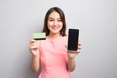 Charming asian woman hand holding smartphone and show credit car Stock Photography