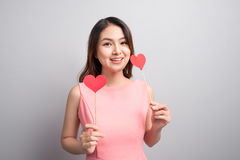 Charming asian woman holding red heart shape. Royalty Free Stock Images