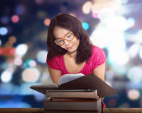 Charming asian woman sitting by wooden table and reading book. Against blurred background Royalty Free Stock Photo