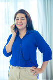 Charming Asian woman is talking on her mobile phone Royalty Free Stock Image