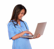 Charming asiatic nurse woman working on laptop Stock Photography