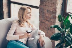 Charming, attractive, pretty, stylish woman, having glass of wine. Charming, attractive, pretty, stylish woman, having glass with wine in hand sitting on couch stock images