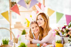 Charming, attractive, pretty, sweet mother and daughter preparing for Easter, hugging, smiling looking at camera, spending, enjoy royalty free stock photo