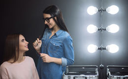 Charming attractive woman looking at her make up artist Royalty Free Stock Photography