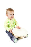 Charming baby. The sitting baby with tambourine on a white isolated background Stock Image
