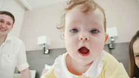 Charming baby crawls on the bed, parents look after their daughter. stock video footage