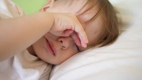 Charming baby falls asleep on white bed in his bed in room at home. concept of sleeping child. child wants to sleep and. Rubs his eyes with his hands. kid royalty free stock photo