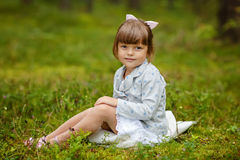 Charming baby girl with brown eyes is sitting on the grass in th Royalty Free Stock Photo