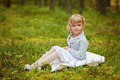 Charming baby girl with brown eyes is sitting on the grass in th Royalty Free Stock Images
