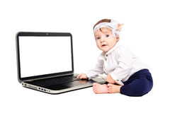 Charming baby girl sitting with a laptop Stock Photography