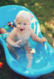 Charming baby having bath in the garden Stock Photos