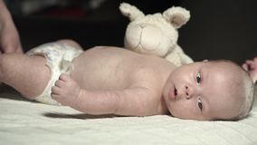 A charming baby lies on a bed with a plush toy and actively moves his arms stock footage