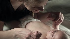 A charming baby lying on the bed, and a young mother holding his hand. A dark room. Close up stock video footage
