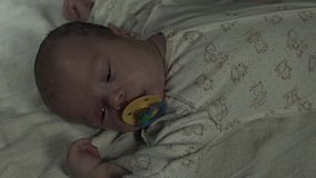 A charming baby with pacifier in his mouth lies on a bed. The light fades slowly stock video