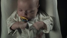 A charming baby with pacifier in his mouth sleeping on the bed. stock video footage