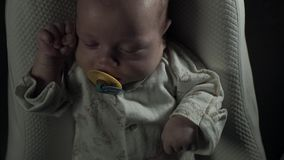 A charming baby with pacifier in his mouth sleeps on the bed. The light slowly gets brighter. The child wakes up and cries stock footage
