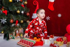 Charming baby in pajamas looking for Christmas gifts Stock Photo