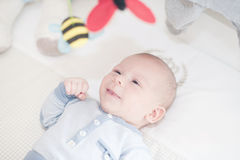 Charming baby playing with a toy lying on back Royalty Free Stock Photo