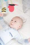 Charming baby playing with a toy lying on back Stock Photo
