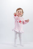 Charming baby in rose dress pointing at camera smiling Stock Photos