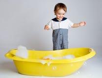 Charming baby standing near bathtub Stock Photo