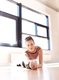 Charming Ballerina in a Training Smiling at Camera. Charming Young Pretty Ballerina in a Training Inside the Dance Studio, Smiling at Camera While Stretching her Stock Photo
