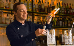 Charming barman pours alcohol from a bottle into a jigger Royalty Free Stock Image
