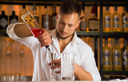 Charming barman pours alcohol from a bottle into a jigger Royalty Free Stock Images