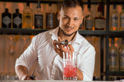 Charming bartender pours alcohol from the jigger into a mixing g Royalty Free Stock Image