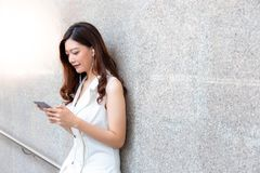 Charming beautiful asian woman. Attractive beautiful girl is listening nice music by using smartphone, earphone at her office royalty free stock images