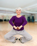 Charming beautiful elderly woman doing exercises while working out playing sports Royalty Free Stock Image